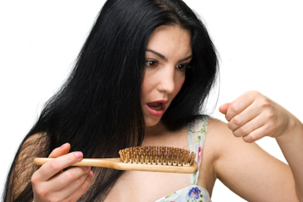 Woman losing hair on hairbrush